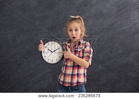 Surprised Little Girl Holding Big Clock And Pointing On It. Time Management, Deadline, Time To Study