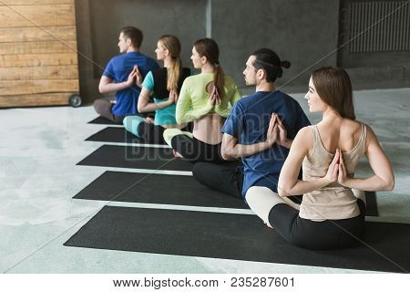 Young Women And Men In Yoga Class, Meditation Exercises. Reverse Prayer Pose, Back And Shoulders Str