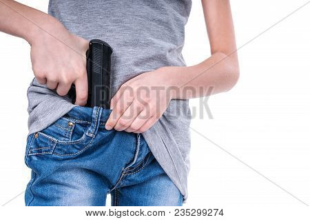 Juvenile Hands Shoved A Real Gun In The Waistband Of Jeans, Close-up, Isolated On A White Background
