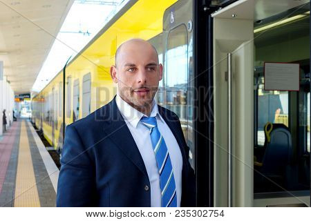 Portrait Of Middle Aged Man In A Business Suit  At The Railway Station In Europe Entering The Open D