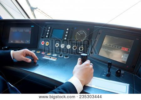 Hands Of Middle Aged Man Driving The Modern Train In Europe