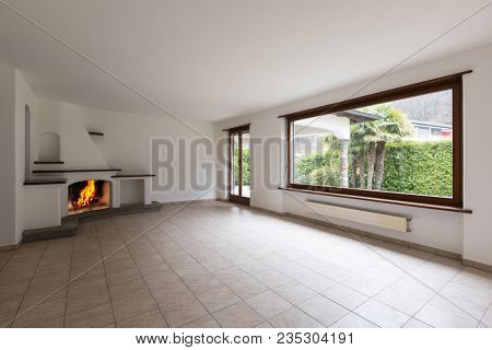 Room with large windows and lit fireplace on a cold winter day. Nobody inside