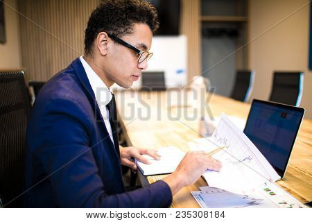 Man In Glasses Successful Economist Or Financier Working With Financial Graphics And Laptop Computer