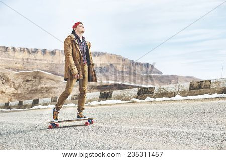 Stylish Happy Young Man In A Cap And Trousers Joggers Rolling Down A Mountain Road On A Longboard, E