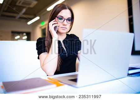 Female Freelance Content Writer Talking Via Mobile Phone With Client And Using Laptop Computer While