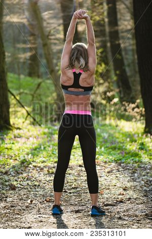 Jogger woman stretching after workout.