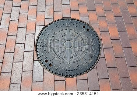 Sewer Manhole Cover On The Tile Ground With Marks Of The Sides Of The World