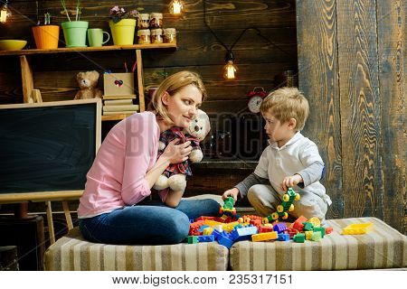 Kindness And Education Concept. Family Play With Teddy Bear At Home. Mom And Child Play With Soft To