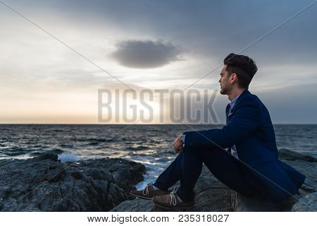 Sad Young Man In Elegant Suit Sits On The Background Of The Sea And Sky. Pensive Guy Meditating Near