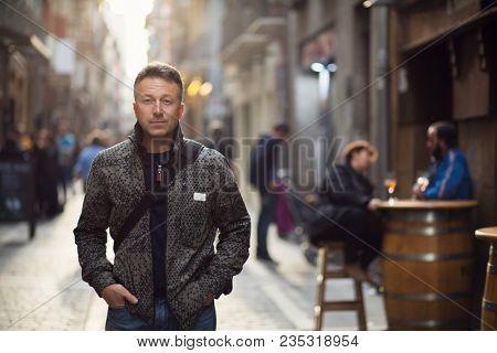 Handsome middle-aged man walking autumn street. Urban male portrait.