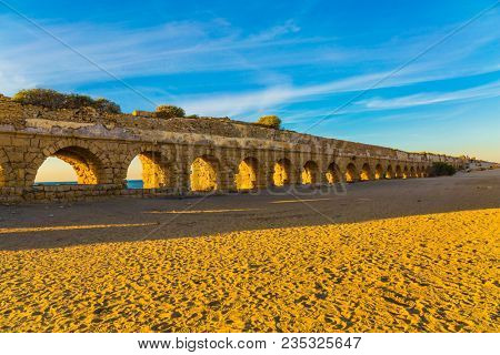 The sandy beach is trampled by tourists.  Ruins of the