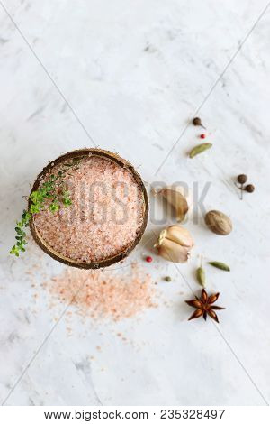 Pink Salt In A Cup With A Sprig Of Thyme, Garlic And Spices On A White Background