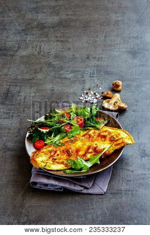 Flat Lay Of Homemade Mushroom Omelette With Salad On Plate Over Dark Concrete Copy Space Background.
