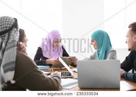 Muslim students with their classmates in library