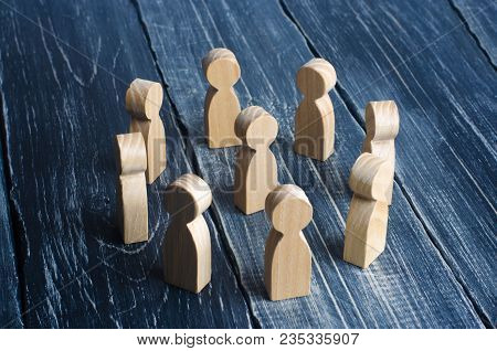 Wooden Curly People Stand In A Circle Around The Person On A Dark Background. The Concept Of Communi