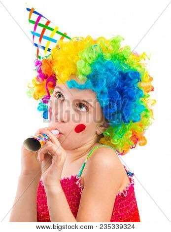 Cheerful young little girl in curly clown wig and party horn blower isolated on white background