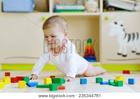 Cute Sad Crying Baby Playing With Colorful Wooden Blocks Toys. New Born Child, Little Girl Looking A