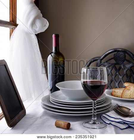 A restaurant still life with wine, bread, chair, table, window and Chalk Menu Board. Square Format