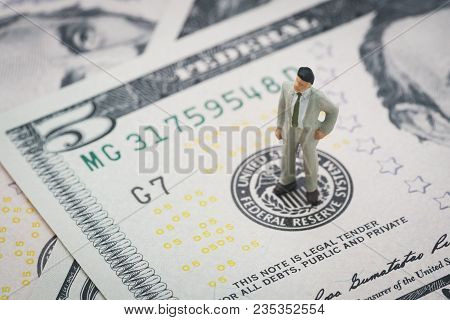 Miniature Businessman Leader Standing And Thinking On Us Federal Reserve Emblem On Five Dollars Bank