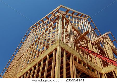 New Residential Construction House Wood Building Frame Against A Blue Sky.
