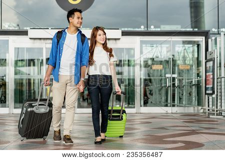 Young Happy Asian Couple Carrying Suitcase Luggage In Airport Terminal. Couple Holding Hand And Trav