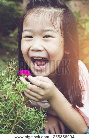 Cute Asian Girl Laughing And Admiring For Pink Blooming Flowers And Nature Around Backyard. Child Ha