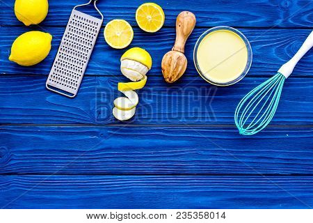 Cook Lemon Curd. Sweet Cream In Bowl, Fruits, Kitchen Utensils Grater And Whisk On Blue Wooden Backg