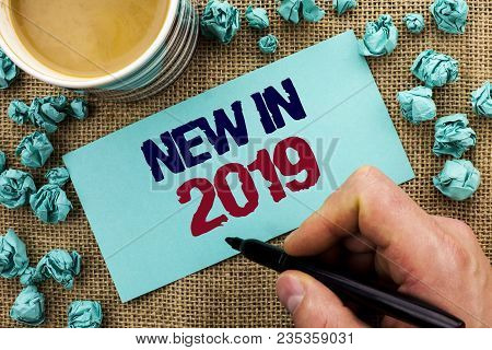 Writing note showing  New In 2019. Business photo showcasing Fresh Era Latest Year Period Season Annual Coming Modern written by Man Holding Pen Sticky Note Paper the jute background Cup poster