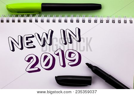 Conceptual hand writing showing New In 2019. Business photo showcasing Fresh Era Latest Year Period Season Annual Coming Modern written Notebook Book the Plain background Marker Pen poster