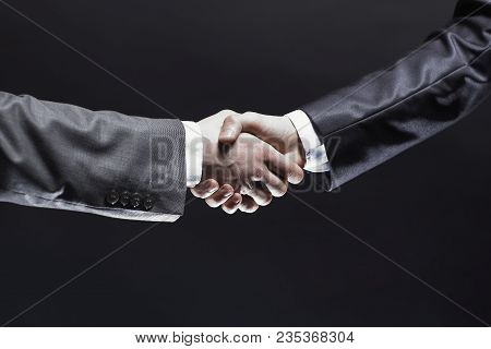 Close Up. Handshake Business Partners.isolated On Black Background.