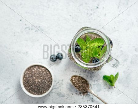 View From Above Chia Water In Mason Jar With Mint And Blueberry On Gray Cement Background.chia Infus