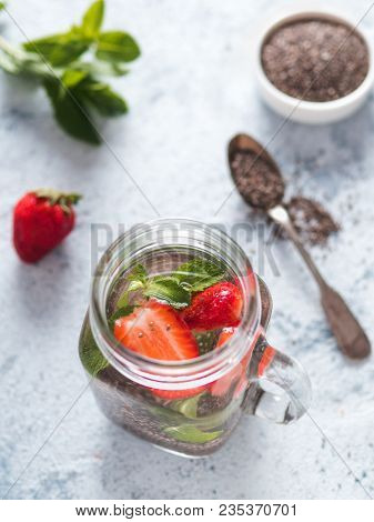 View From Above Chia Water In Mason Jar With Strawberry And Mint On Gray Cement Background. Chia Inf