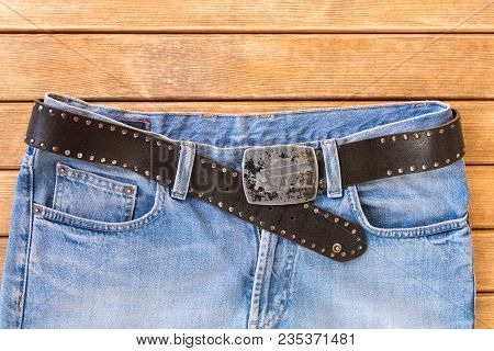 Blue Jeans With A Black Leather Strap . On Wooden Background .