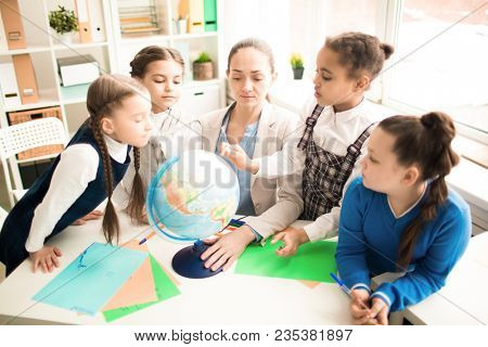 Cute pupils and teacher in classroom with globe at the primary school