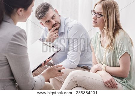 Upset Young Woman Talking To A Female Psychologist, With Her Husband By Her Side During Marital Coun