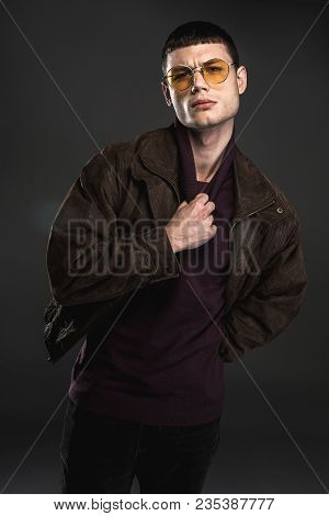 Portrait Of Sure Young Male Keeping Collar Of Sweater By Hand. He Isolated On Black Background. Cert