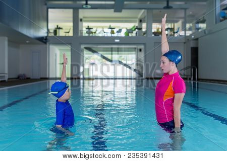Swimming Lesson. Cute Little Boy Learning To Swim With Swimming Instructor