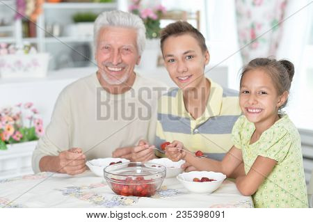 Portrait Of Grandfather And Grandchildren Eating Fresh Strawberries At Kitchen