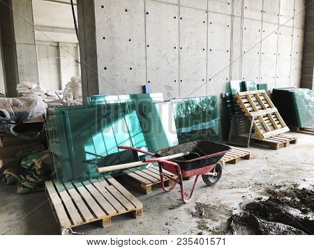 Large Glass, Sandbags And Building Materials At The Construction Site. Material For Repairs In An Ap
