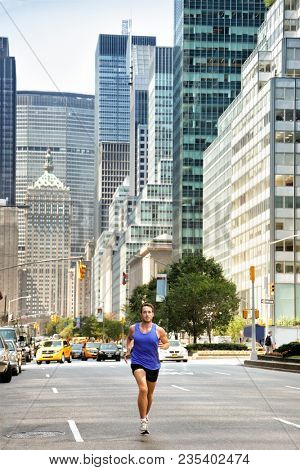 Running man runner in New York City. Urban male runner in busy street in New York NYC. Young adult jogging in traffic on Manhattan during summer training for Marathon.