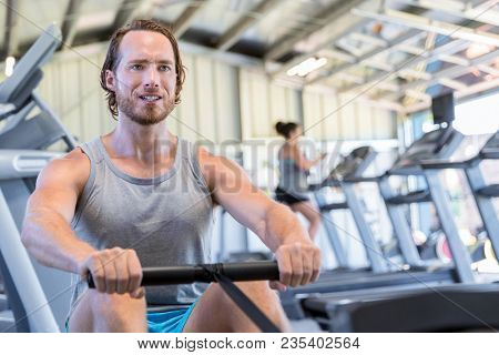 Fitness man training on rowing machine at gym. Athlete working out his cardio on rowing machine in fitness gym club.