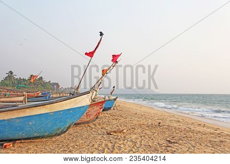 Bright Fishing Boats Stand On The Sand In India, Goa. Multicolored Indian Boat On The Background Of
