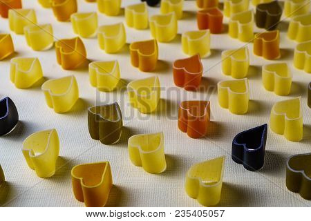 Minimalism style. Repetition concept. View from above on pasta pattern with heart shape; on colored background. poster