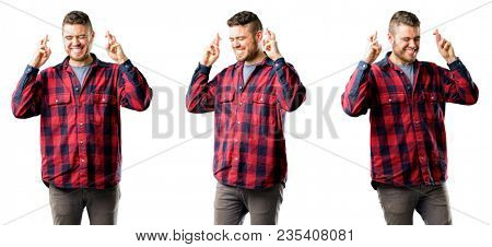 Young man with crossed fingers asking for good luck isolated over white background, collage composition