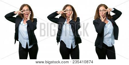 Middle age business woman looking at camera through her fingers in victory gesture winking the eye and blowing a kiss over white background