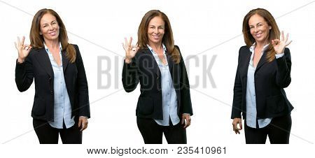 Middle age business woman doing ok sign with hand, approve gesture over white background
