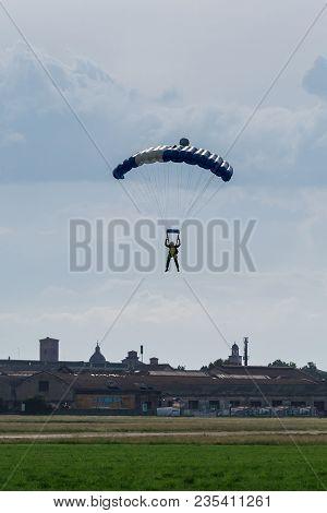 Reggio Emilia, Italy - May 2017: Parachutist With Blue Parachute Near To The Ground Preparing For La