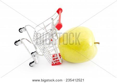 Shopping Cart With Big Green Apple On White. Buying Fruits From Supermarket. Self-service Supermarke
