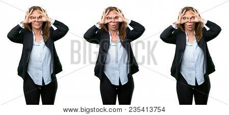 Middle age business woman looking at camera through her fingers in ok gesture. Imitating binoculars over white background