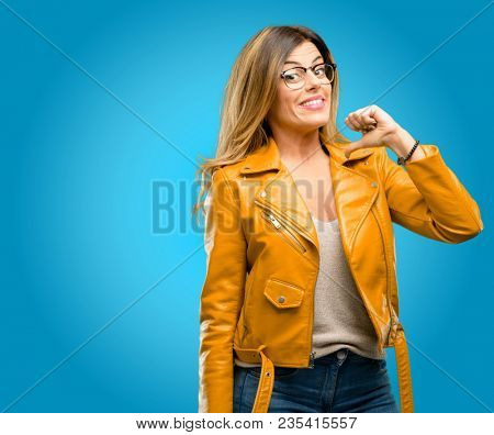 Beautiful young woman proud, excited and arrogant, pointing with victory face, blue background